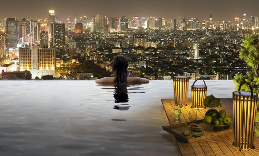 Young woman in outdoor swimming pool with city view